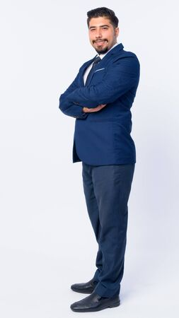 Full body shot profile view of happy bearded Persian businessman looking at camera