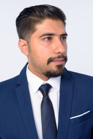 Face of handsome bearded Persian businessman thinking Stock Photo