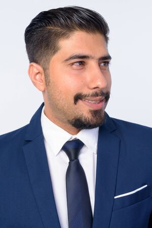 Face of happy bearded Persian businessman thinking