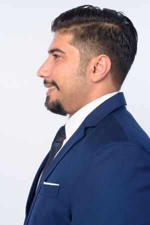 Closeup profile view of happy bearded Persian businessman smiling Stock Photo