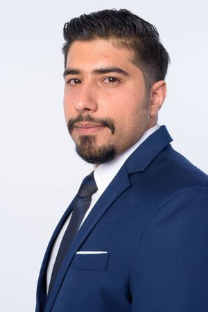 Closeup profile view of handsome bearded Persian businessman looking at camera Stock Photo