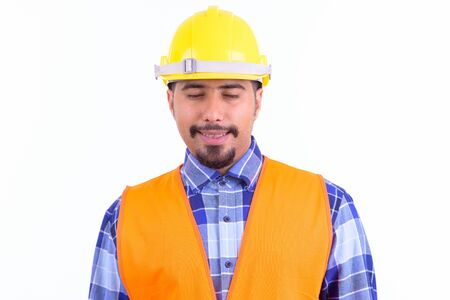 Face of happy bearded Persian man construction worker relaxing with eyes closed Stock Photo