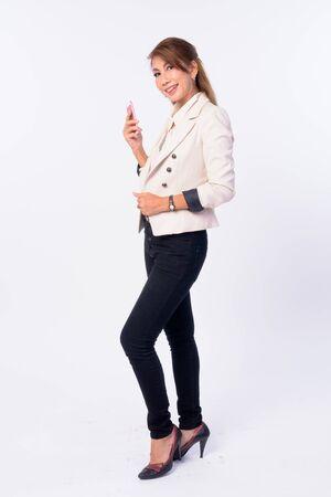 Full body shot of happy mature Asian businesswoman using phone