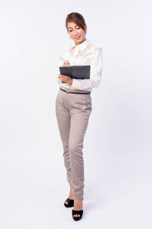 Full body shot of happy mature Asian businesswoman writing on clipboard