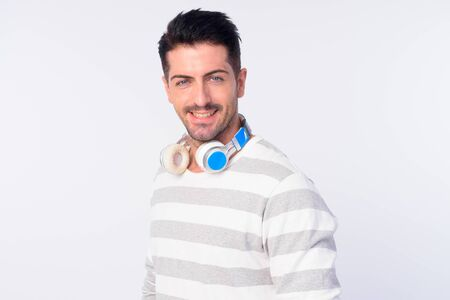 Face of happy handsome bearded man with headphones smiling