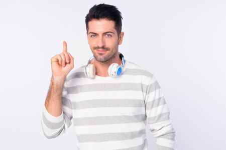 Portrait of handsome bearded man with headphones pointing up
