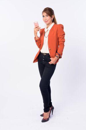 Full body shot of mature Asian businesswoman using phone Фото со стока