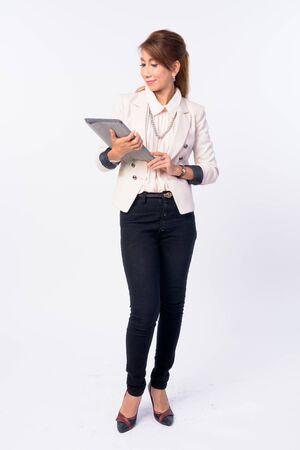 Full body shot of mature Asian businesswoman using digital tablet