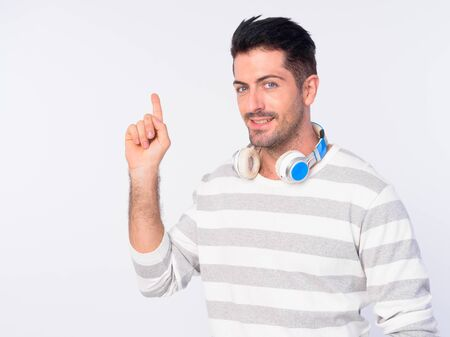 Portrait of happy handsome bearded man with headphones pointing up Stock Photo