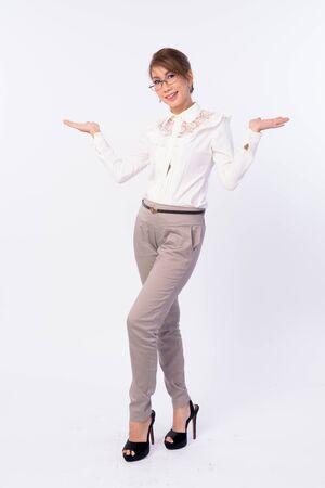Full body shot of happy mature Asian businesswoman with eyeglasses comparing something