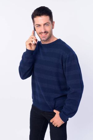 Portrait of happy handsome bearded man talking on the phone