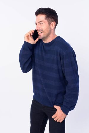 Portrait of happy bearded man thinking while talking on the phone