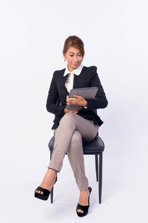 Full body shot of mature Asian businesswoman sitting and using digital tablet Banco de Imagens