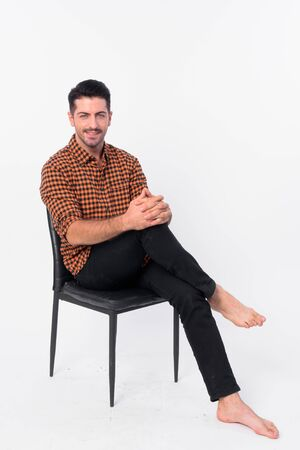 Full body shot of handsome bearded hipster man sitting on chair