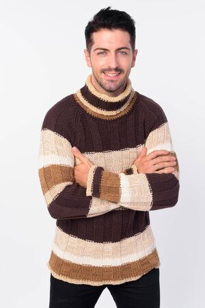 Happy handsome bearded man smiling with arms crossed ready for winter Stock Photo