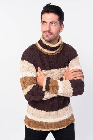Handsome bearded man thinking with arms crossed ready for winter Stock Photo