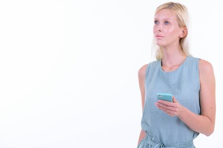Portrait of young beautiful blonde woman thinking while using phone