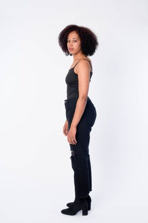 Full body shot profile view of young beautiful African woman looking at camera Imagens