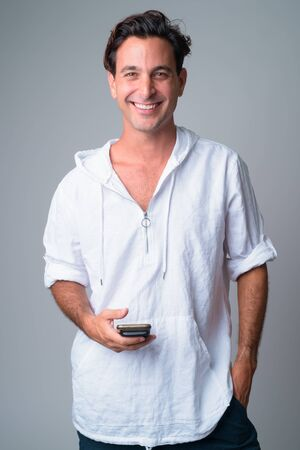 Portrait of happy handsome Hispanic man using phone