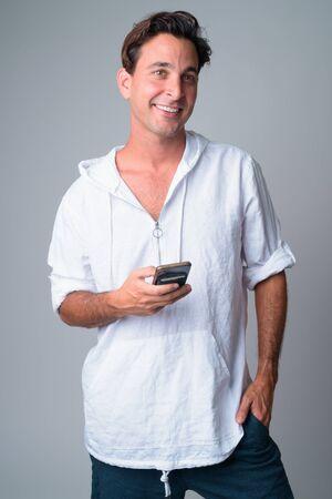 Portrait of happy handsome Hispanic man thinking while using phone