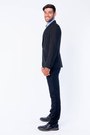 Full body shot profile view of happy young bearded Persian businessman looking at camera