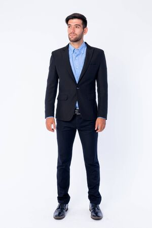 Full body shot of young bearded Persian businessman thinking Stock Photo