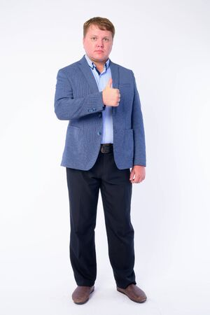Full body shot of overweight businessman in suit giving thumbs up