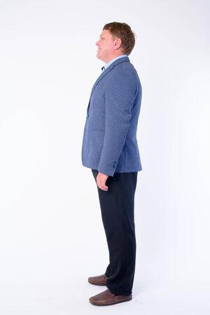 Full body shot profile view of happy overweight businessman in suit smiling