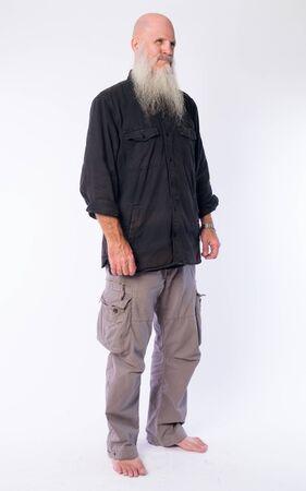 Full body shot of mature bald man with long gray beard thinking