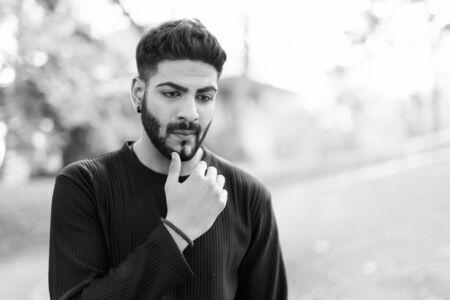 Junger gutaussehender indischer Mann, der mit der Hand am Kinn im Park denkt