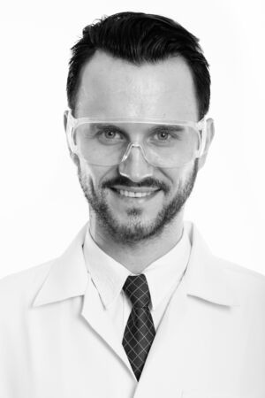 Face of young happy man doctor smiling while wearing protective glasses