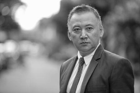 Uomo d'affari giapponese maturo che pensa nelle strade all'aperto