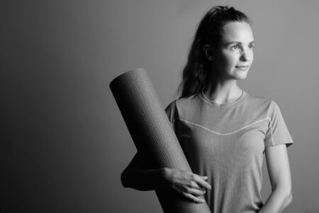 Young beautiful woman holding exercise mat for yoga training Stockfoto