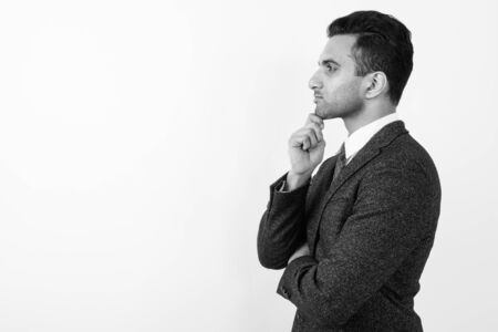 Young handsome Indian businessman against white background Imagens