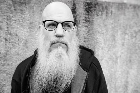 Mature bald man with long gray beard wearing eyeglasses outdoors Banque d'images