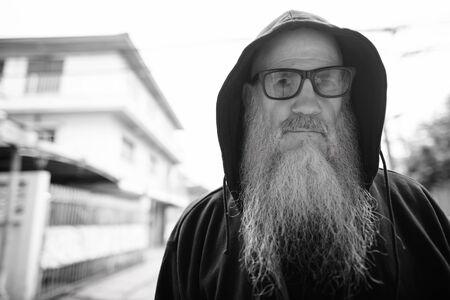 Mature bald man with long gray beard wearing sunglasses outdoors