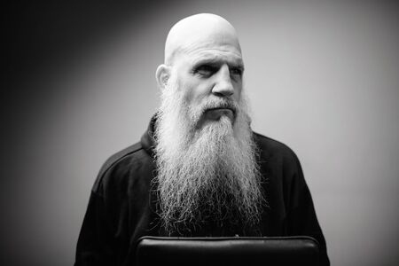 Portrait of mature bald bearded man thinking with dramatic shot in black and white