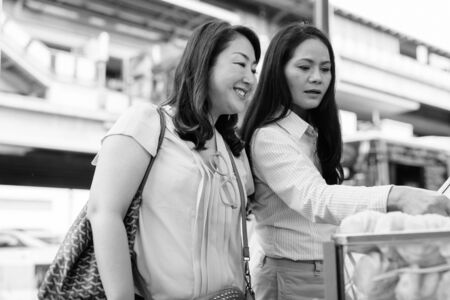 Two mature Asian women shopping together in the street market