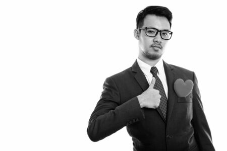Studio shot of young Asian businessman giving thumb up with red heart on chest 版權商用圖片