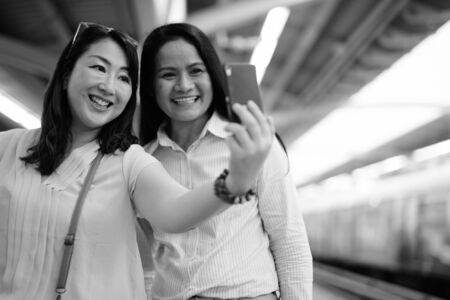 Two mature Asian women together at the train station using mobile phone Stock Photo