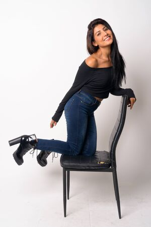 Full body shot of happy young Persian woman kneeling on the chair