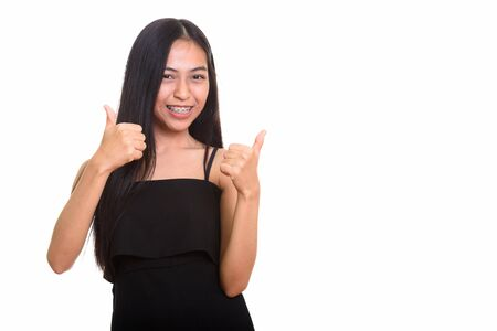 Studio shot of young happy Asian teenage girl smiling and giving