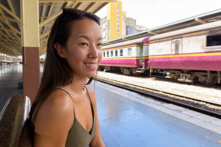 Young tourist woman exploring the city of Bangkok at train station