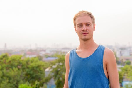 Young handsome man with blond hair relaxing outdoors