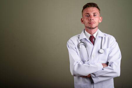 Portrait of young man doctor against colored background Reklamní fotografie - 131131373