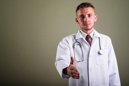 Portrait of young man doctor against colored background Reklamní fotografie - 131131828