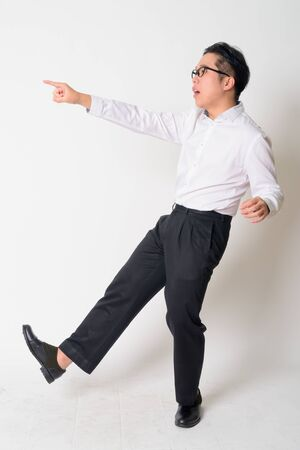 Portrait of stressed young Asian businessman with eyeglasses running away