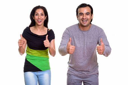 Studio shot of happy Persian couple smiling and giving thumbs up