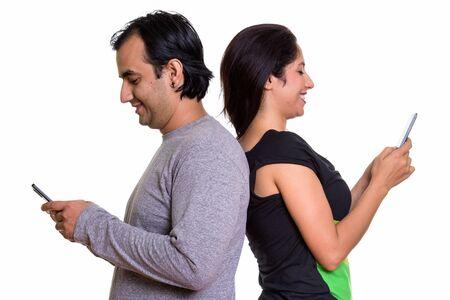 Feliz pareja persa sonriendo mientras usa teléfono móvil juntos b Foto de archivo