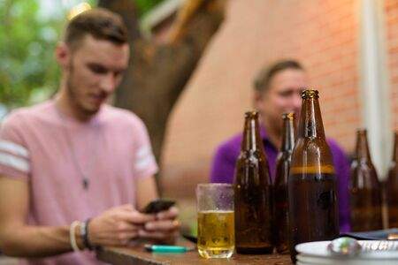 Happy man sitting and using phone outdoors while having beer focus on foreground 版權商用圖片
